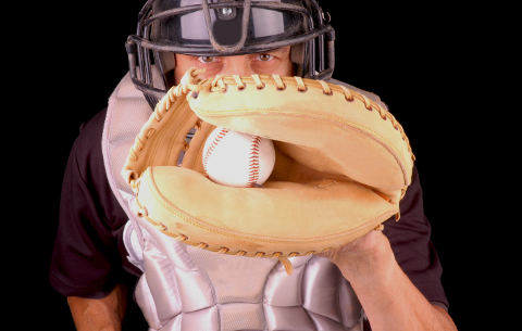 Baseball catcher in gear with caught pitch in mitt